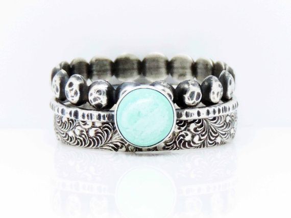 This is a rustic sterling and turquoise ring of my own design. The stone comes from the Kingman mine in Arizona. The main ring has a double band with a centered bezel set stone and is completed by a hammered dot band AND a wide floral fern pattern band to stack. These are very nice because you can wear them separate or together! Awesome set! Bands have been oxidized (darkened and then polished back) for that vintage/antique feel of history!  The design of this ring can be used as a…