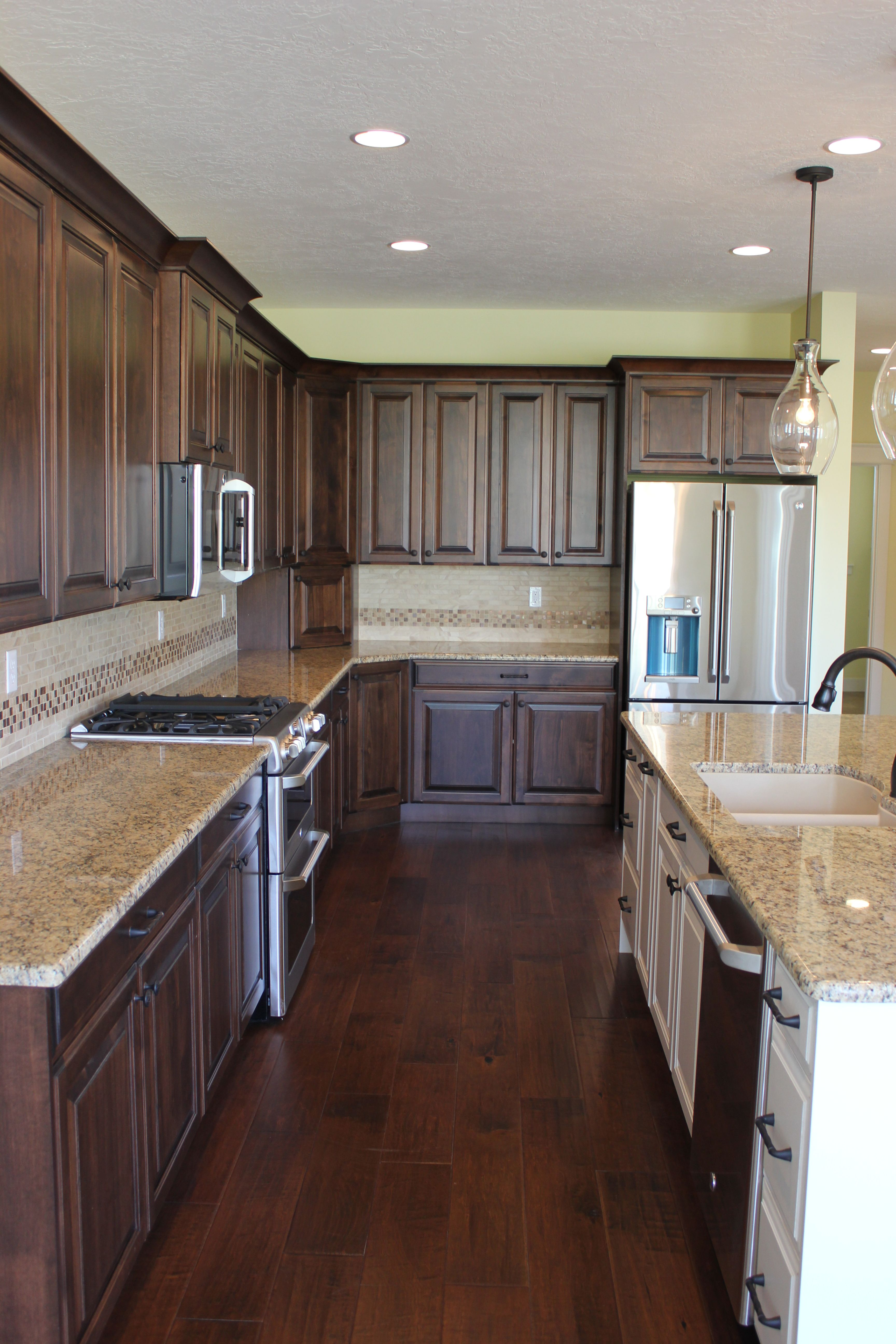 Dark brown perimeter cabinets with painted island and ... on Black Granite Countertops With Brown Cabinets  id=49724
