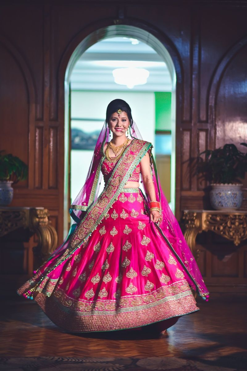 Bride twirling in red lehenga with gold motifs