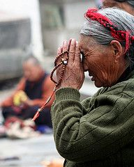 Tibet - Lady praying in front of temple in Lhasa
