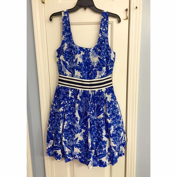 """NWT Juicy Couture Silk Blue Hyacinth Floral Dress Brand new with tags (and original Juicy dress bag) beautiful 100% silk Juicy Couture """"Hyacinth"""" blue and white sleeveless floral print dress with shiny silk lining with ruffle at bottom, pockets, and black and white stripe waistband. Very luxurious feel, super flattering, fit and flare. One of Juicy's best dresses! Wish I could keep it but it doesn't fit me. Size 0, also available in a size 2. Juicy Couture Dresses"""