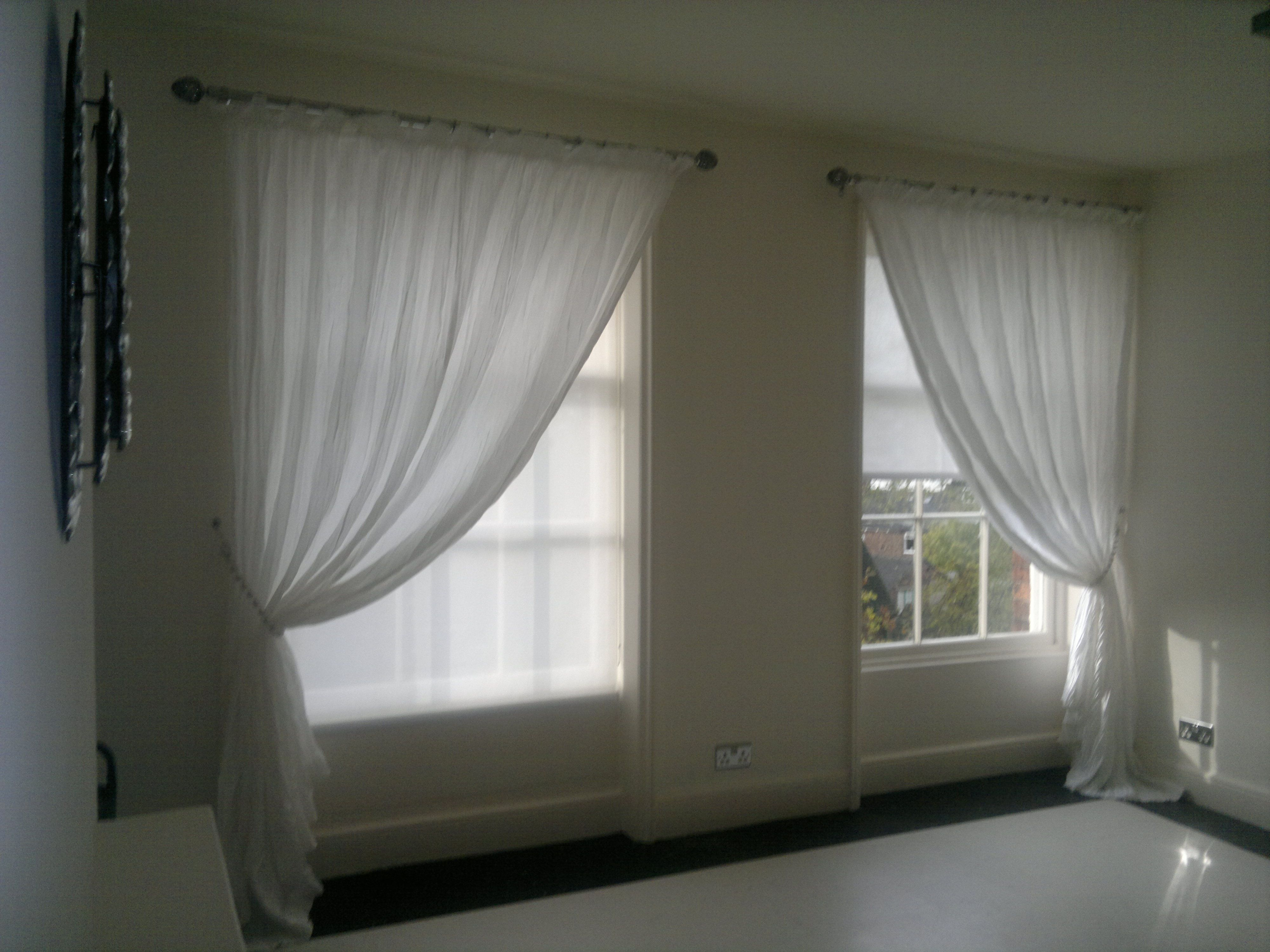 Sheer voiles are mounted over functional roller blinds a single