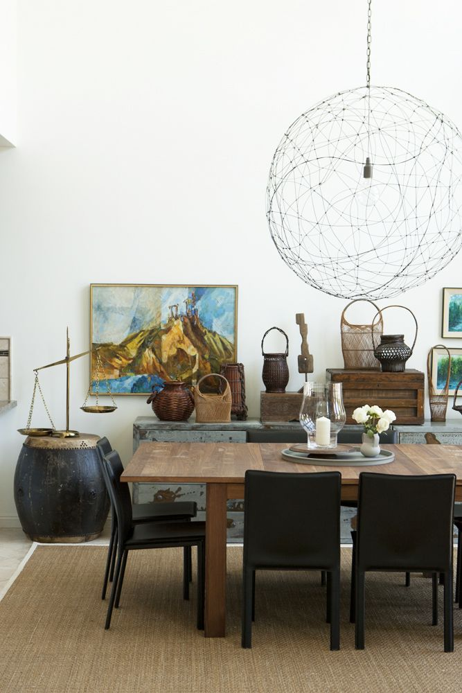 layered neutrals in dining room: vintage woods, metals, leather chairs, baskets.  Airy modern light fixture