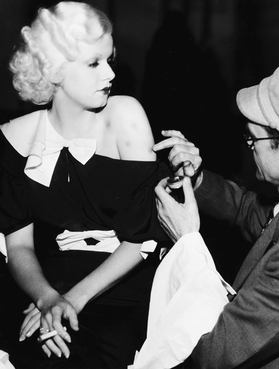 The makeup artist applying bruises to Jean Harlow on the
