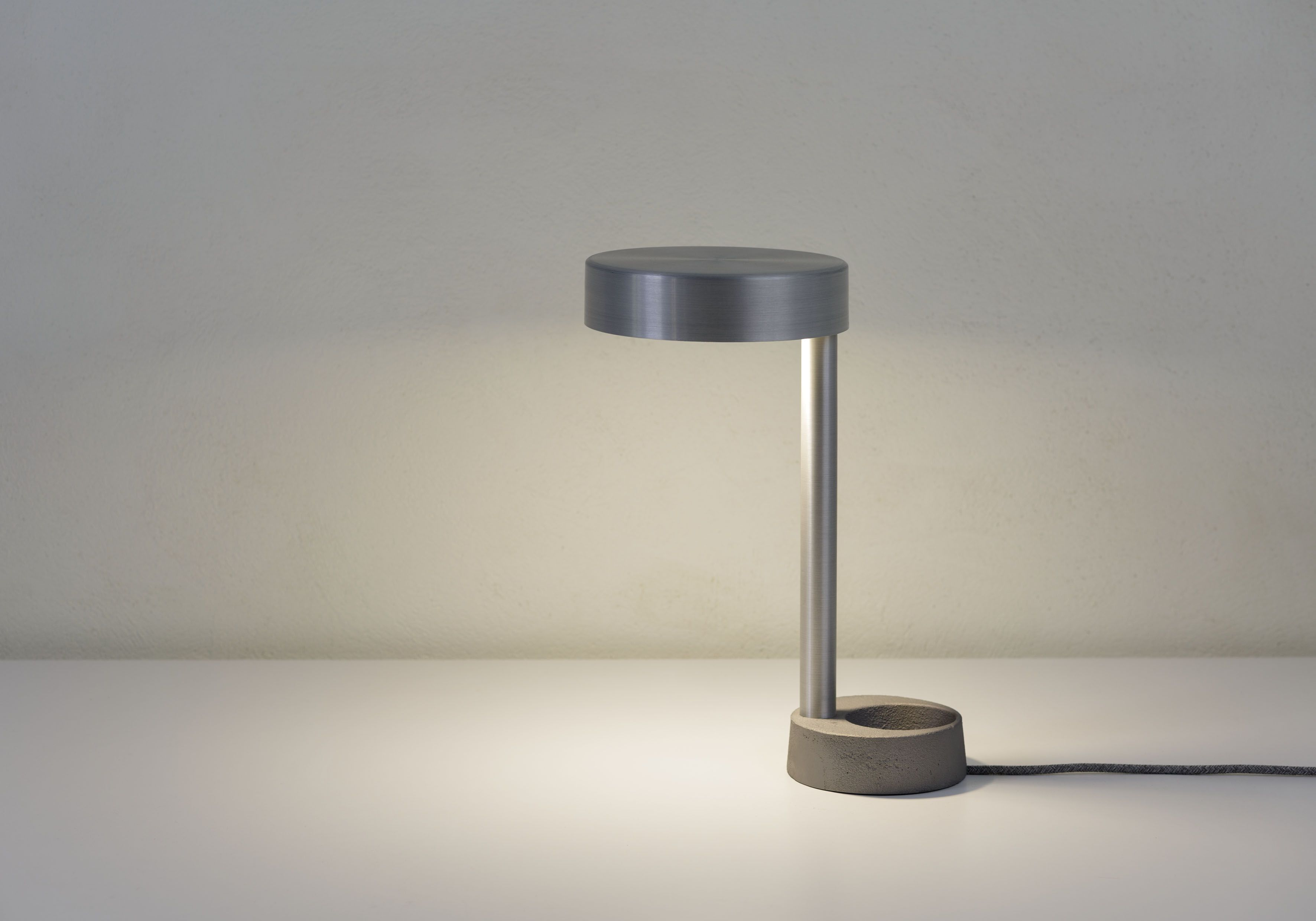 Reading lamp LIGHT. Minimal in form, design and manufacturing. Visually lightweight. Used materials rustic cast iron and smooth aluminum, contrast creates interplay.  Material: cast iron, aluminum, LED bulb. Dimensions: 320 X H 500 mm Weight: 4 kg Technical: 1 x LED bulb 4W - 7W Materials: Cast iron, aluminum, 1,5 meter textile electrical wire.