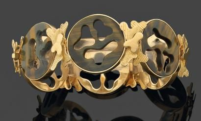 WOLFERS. Années 1960     BRACELET articulé composé de six maillons ronds en or jaune 18 kts ornés au centre de plaques de quartz oeil de tigre chatoyant repercées d'un décor nuagé et réunis par des motifs nuages en or uni ou strié. Travail belge. Poinçon de Maître.