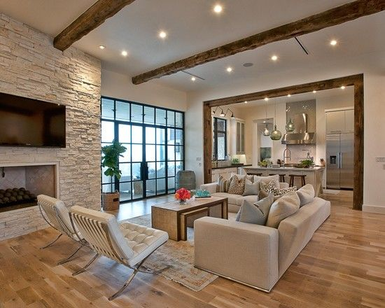 White stone walls around fireplace and white Barcelona chairs