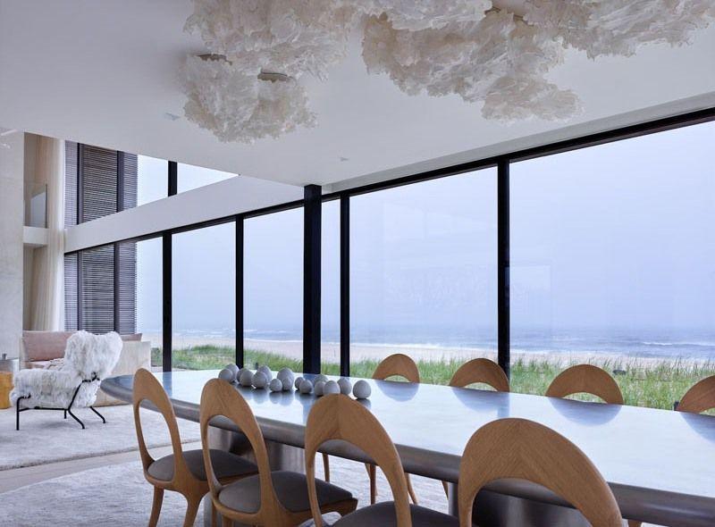 Maison en bois avec de grands espaces vitrés bordant lu0027océan à New