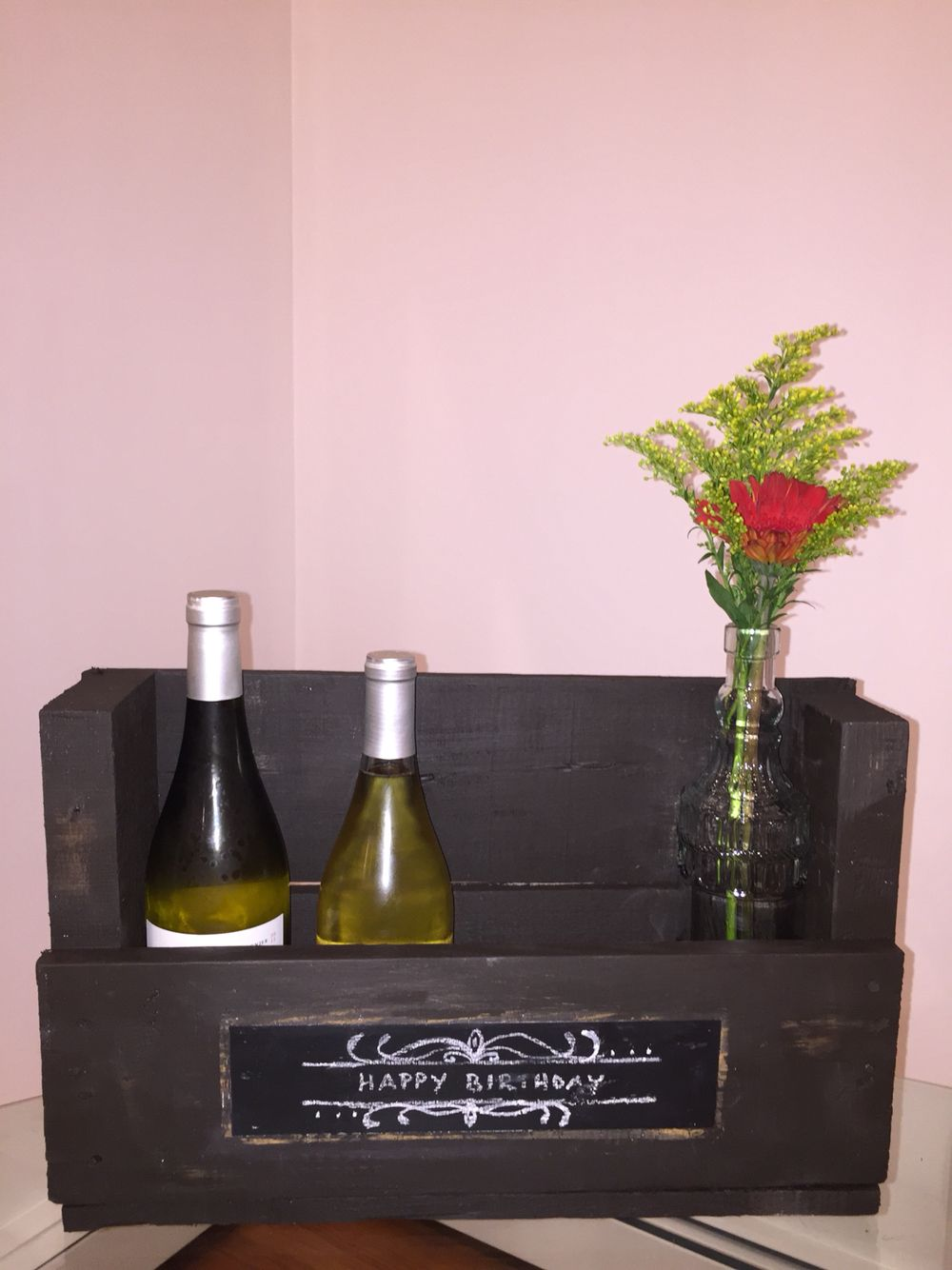 DIY wine bottle rack made from a pallet. Chalk design on front