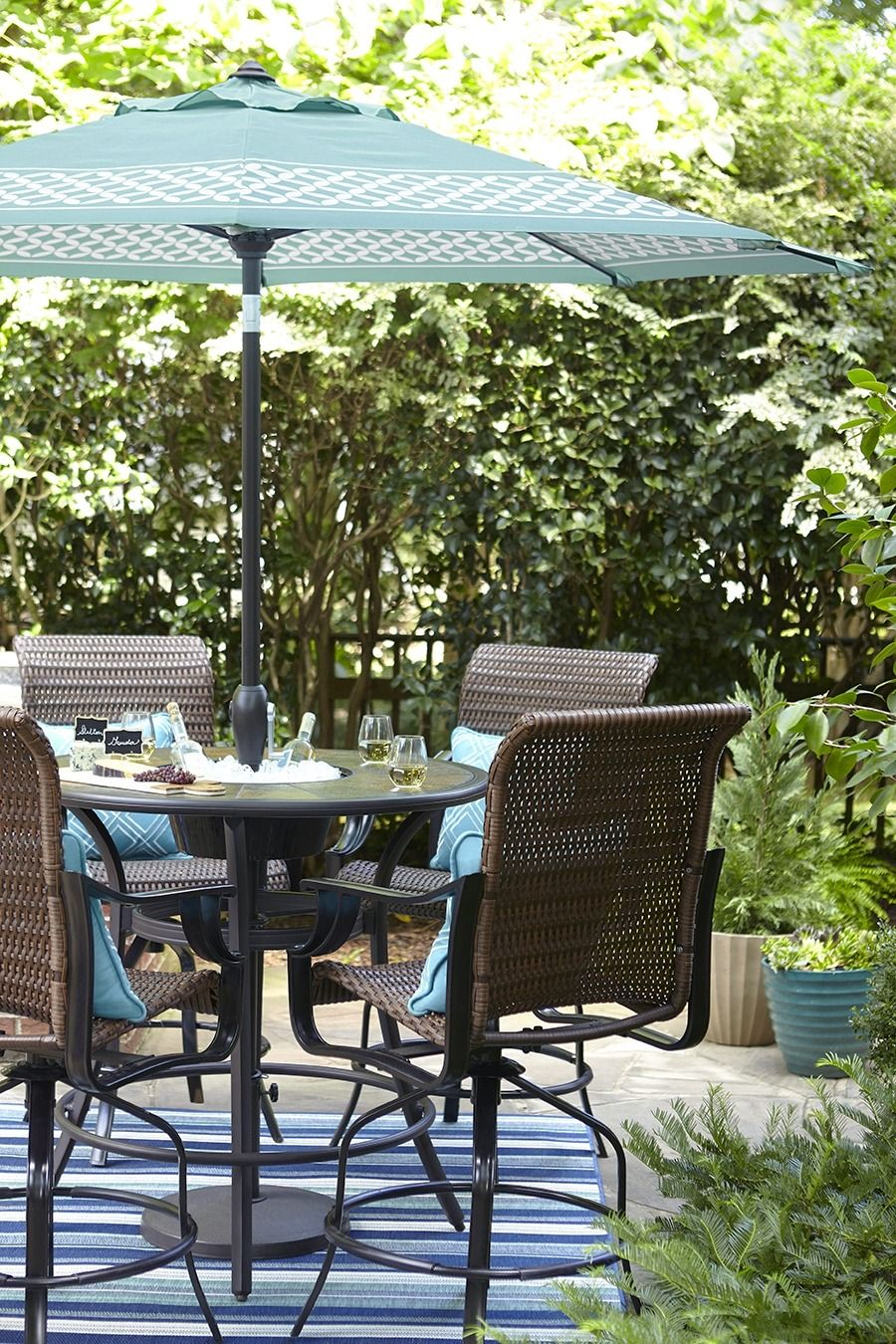 A Bar Height Patio Table Features An Umbrella For Shady Downtime