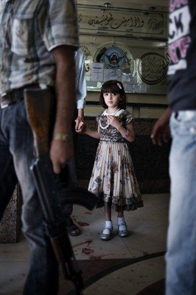 Alession Romenzi/ UNICEF-Foto des Jahres 2012    Syrien: Kinder zwischen den Fronten  Das Unicef-Foto 2012, aufgenommen vom italienischen Fotografen Alessio Romenzi. Er reiste durch Syrien, ein Land, in dem seit knapp zwei Jahren Bürgerkrieg herrscht. Sein Fokus lag dabei vor allem auf den Kindern, die von den Kämpfen betroffen sind. So wie dieses Mädchen im Dar-al-Shifa-Hospital in Aleppo. Mit ängstlichem Blick steht es in dem Krankenhaus, das bereits mehrfach Angriffsziel war.