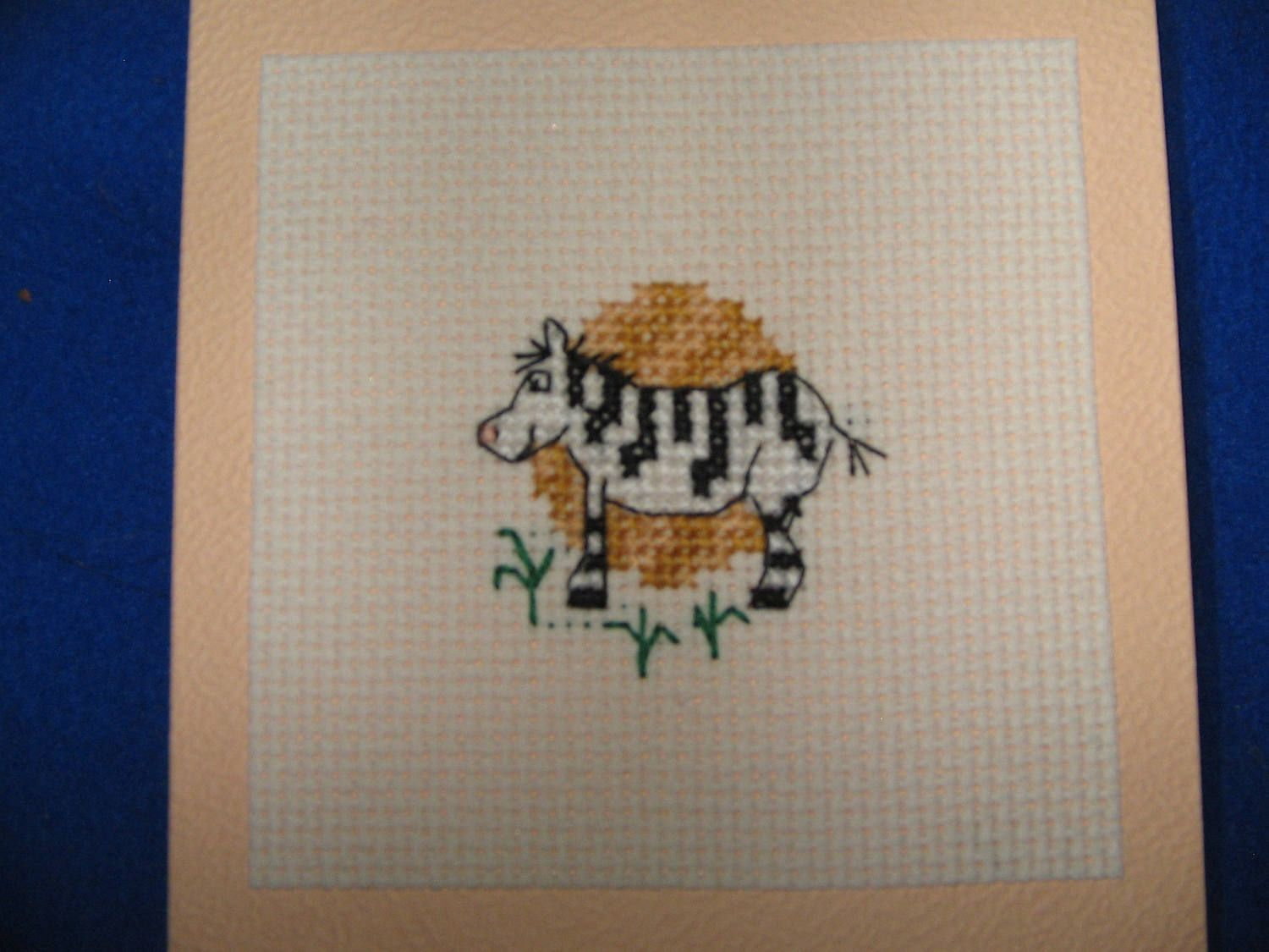 Zebra Stitched motif card on an orange background by Fruityknittedness on Etsy
