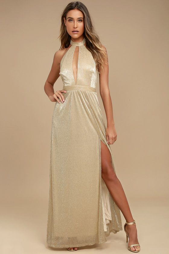 Shine bright and far in the Be A Star Gold Halter Maxi Dress! Beige knit. with metallic gold threading. sparkles as it forms a tying halter neckline and plunging bodice with open back. A banded waist tops a cascading maxi skirt with side slit. Hidden back zipper/clasp.