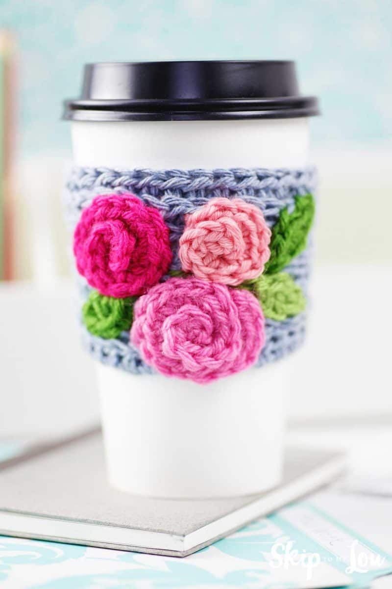 Crochet Coffee Sleeve With Roses On White Take Out Cup Sitting On Desk Diy Crochet Gifts Crochet Rose Pattern Coffee Sleeve Pattern
