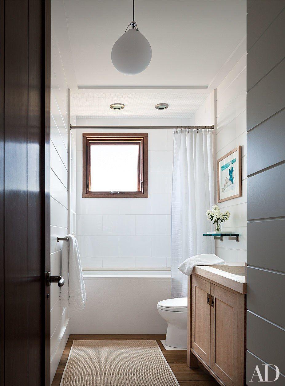 A Louis Poulsen pendant light hangs in a white-tiled guest bath in ...