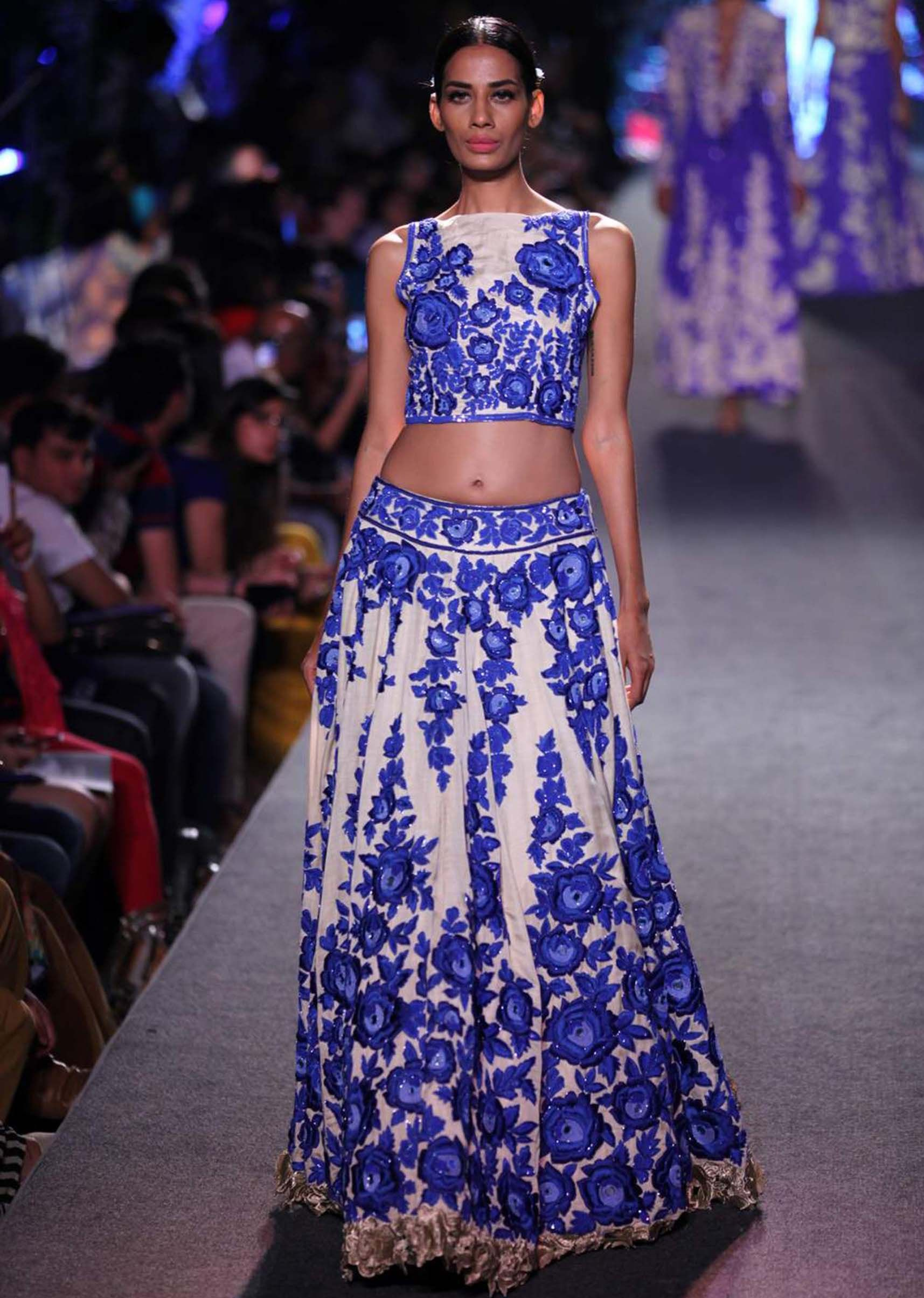 Model in cream lehenga with blue rose motif embroidered walks the ...