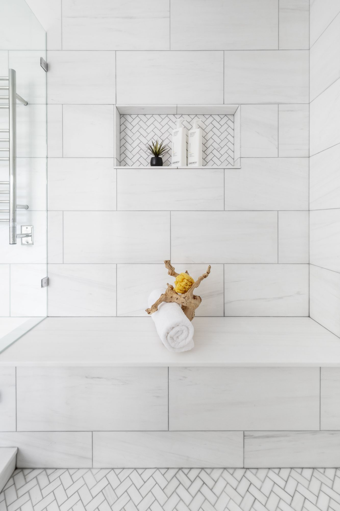 Photo of Sophisticated and fresh-looking Bianco Dolomiti marble, used in mixed formats, makes this master a clean and classic space to renew in. Design by Ayelet Rosen and Michal Abehsera. #showertiles
