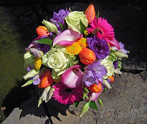 Spring color is all abloom with pale green roses, hot pink daisies, bright yellow button mums, bright orange tulips, pink mini calla lilies, purple lisianthus, and purple freesia.  Flowers by A Floral Affair - www.afloralaffair.com #pdxweddings #weddingbouquet