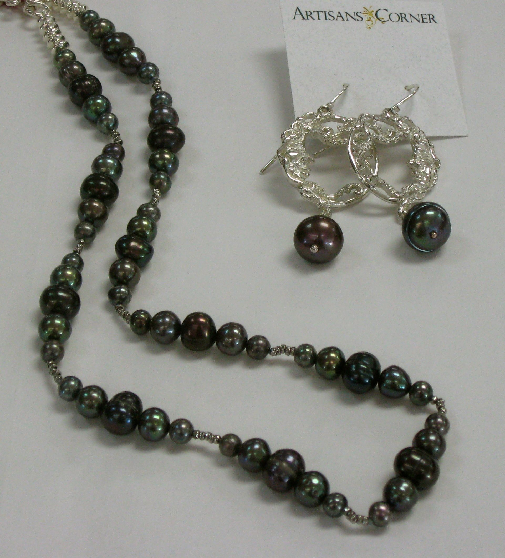 Jack Dokus woman in the moon earrings and Ruth Mary Pollack black pearl necklace.