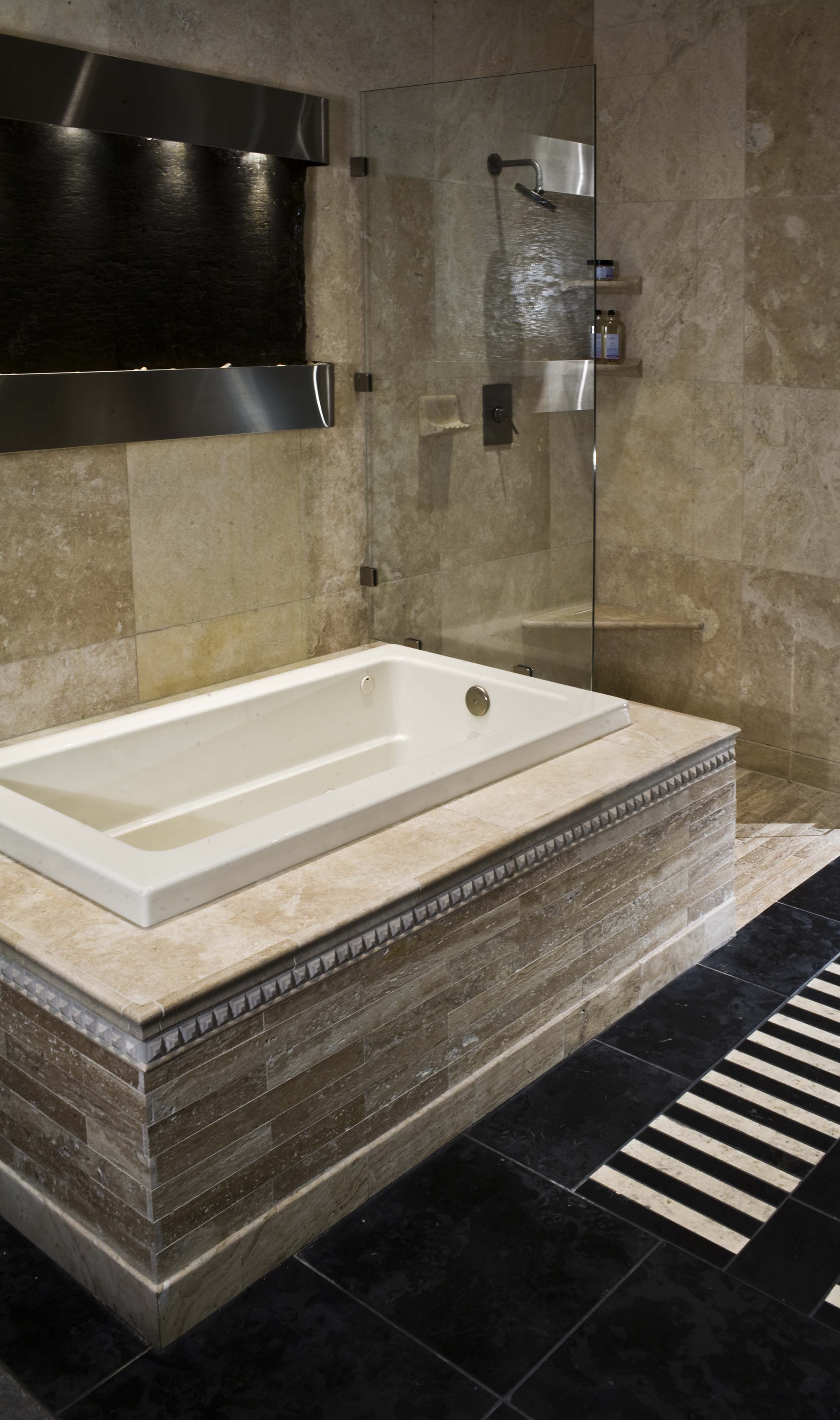 travertine bath paired with charcoal floor tile and a waterfall