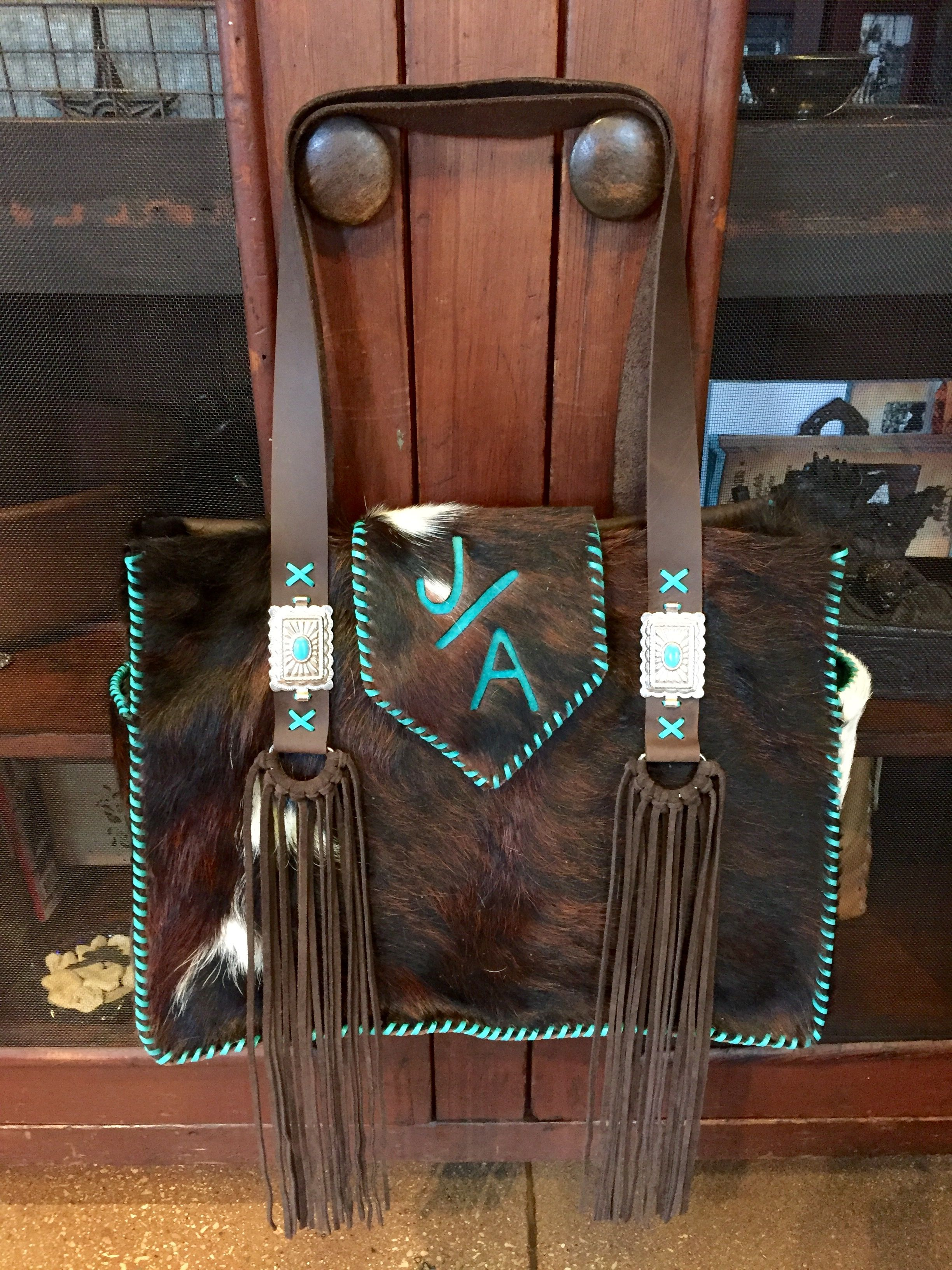 The Buckaroo Diaper Tote stitched in turquoise leather lace, with the owners brand on the flap and exterior side pockets lined in suede. From Go West Designs.