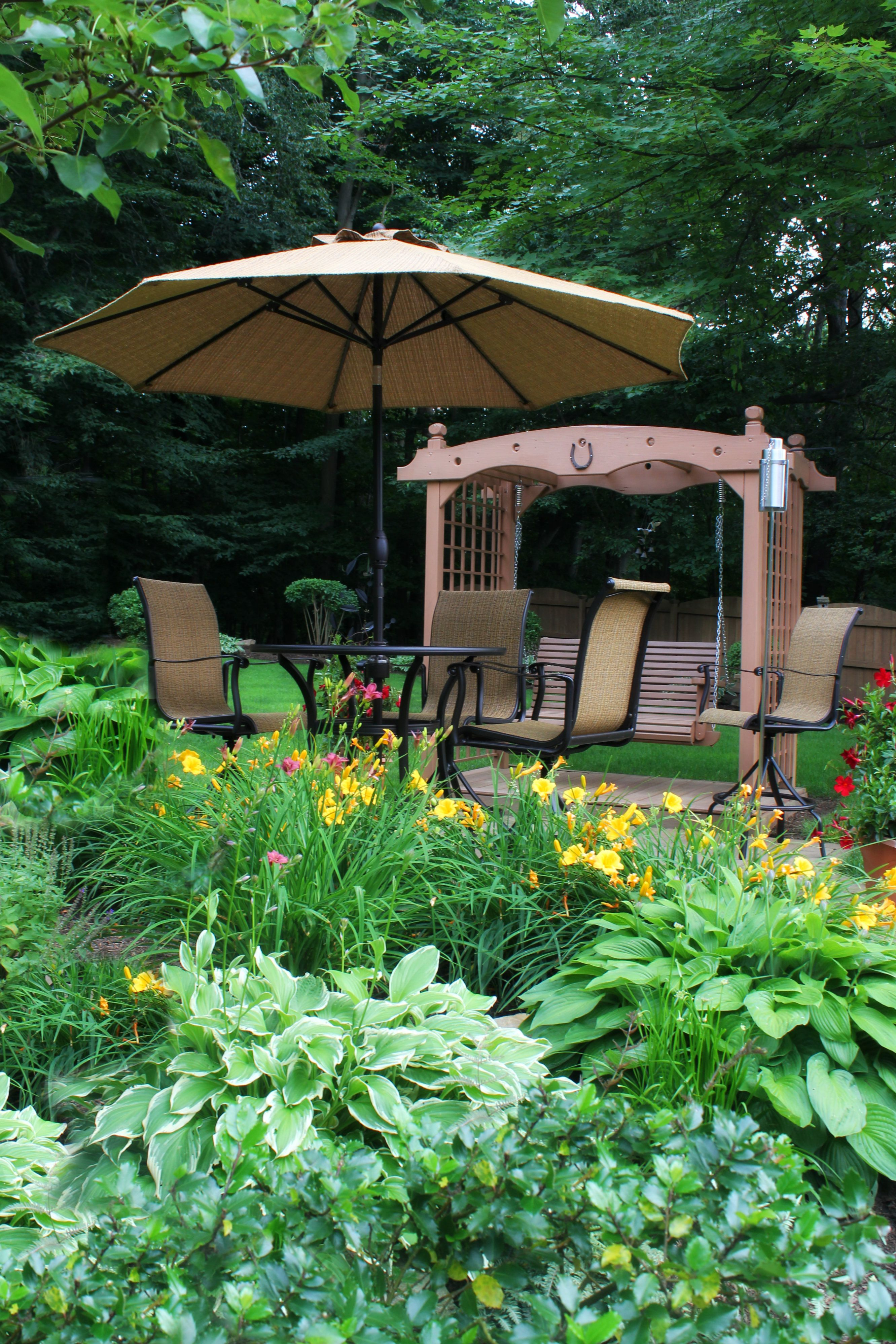 Adding perenials to enhance the setting of a cafe umbrella table and