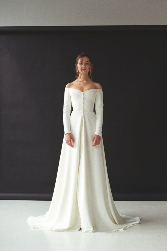 Modern off-shoulder wedding dress with a slit Off-the-shoulder long sleeve crepe bridal gown Minimalist button front wedding gown SERENA