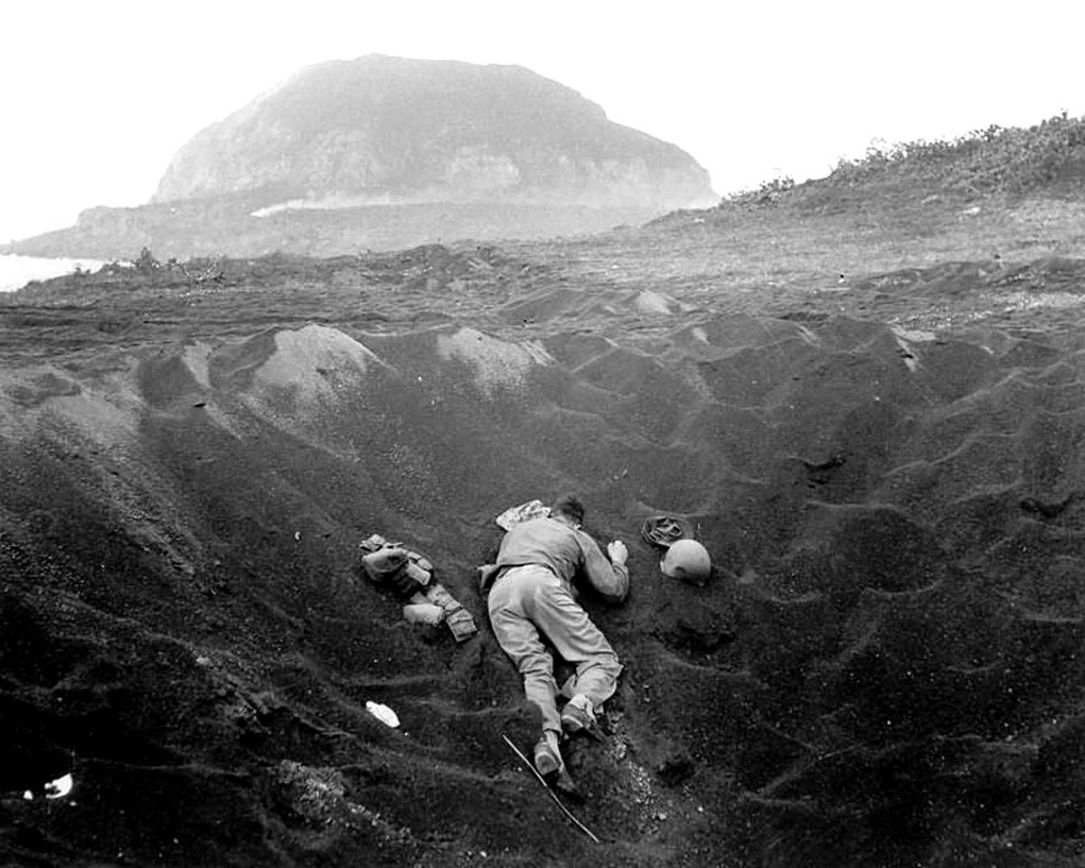 A us marine lies dead in a crater on the beach during the battle marine lies dead in a crater on the beach during the battle of iwo jima codenamed operation detachment mount suribachi can be seen in the background sciox Image collections