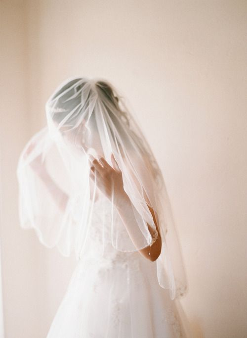 Bride facing the window with veil over her head while she holds it out a bit with her hands under it. I DIE! gorgeous!