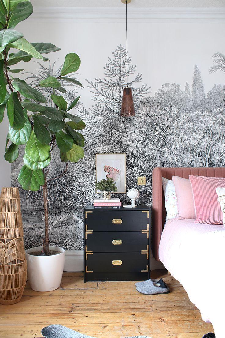 bedroom with black bedside table and fiddle leaf fig with pink bed and wall mural