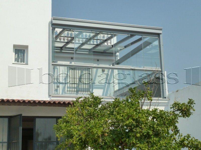 Terraza Acristalada Con Cortinas De Cristal Sin Perfiles Verticales Y Techo Movil De Cristal Fachada Vidrio Patios Cubiertos Fachadas De Casas Modernas