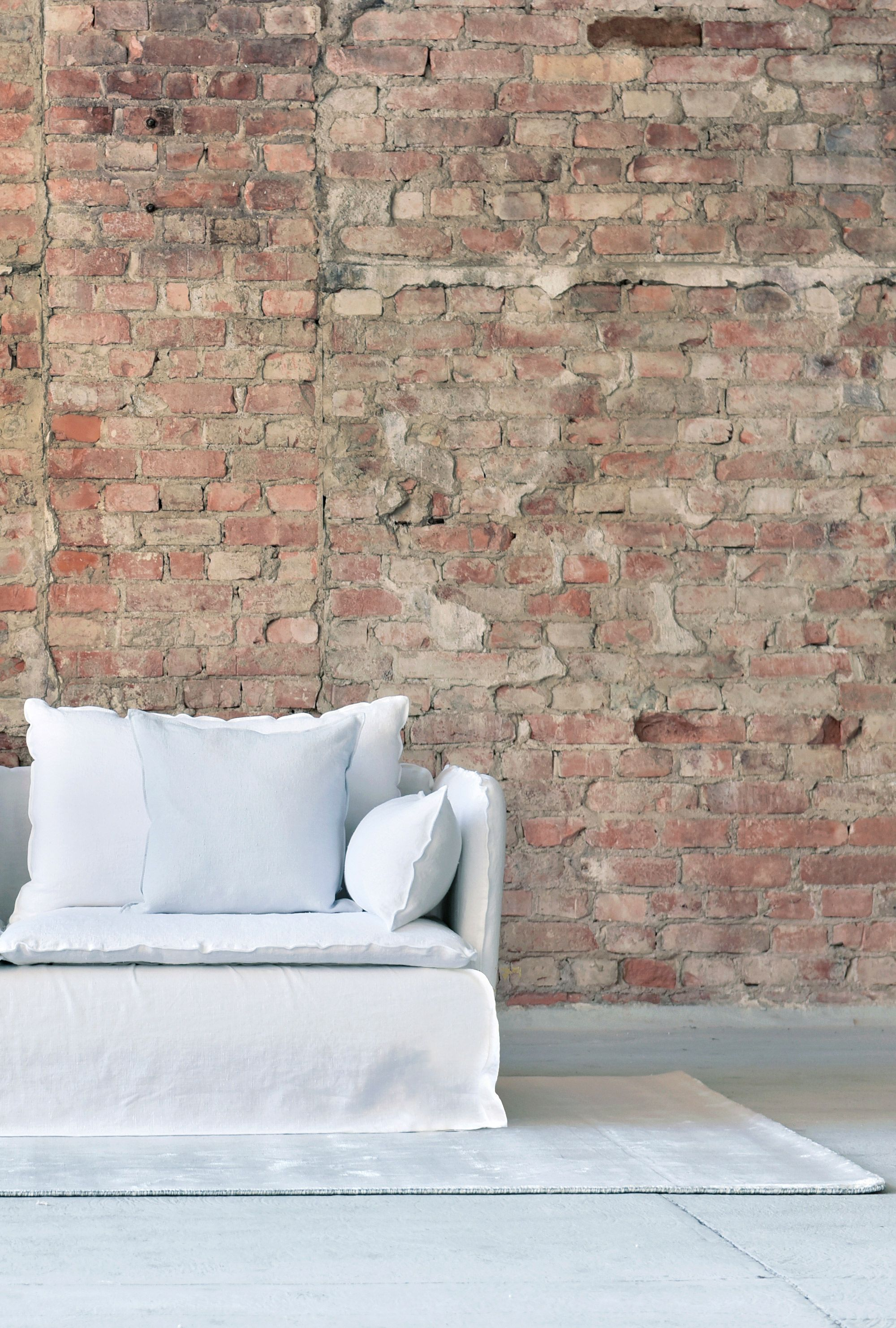white linen sofa red brick wall