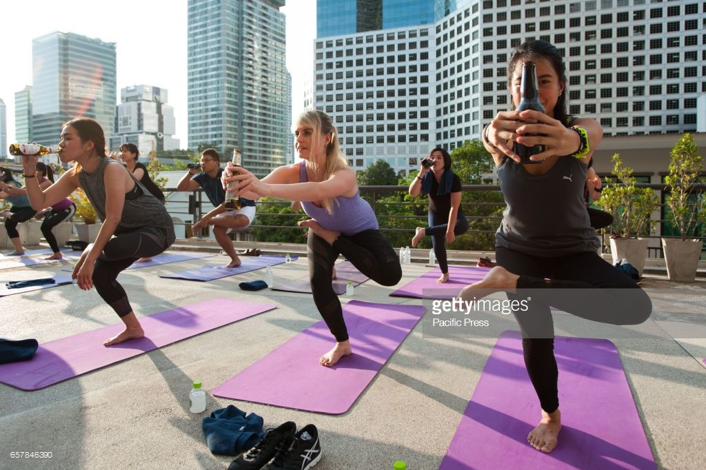 Participants In A Beer Yoga Course Perform A Yoga Exercise With A Yoga Courses Yoga Poses Yoga Fitness