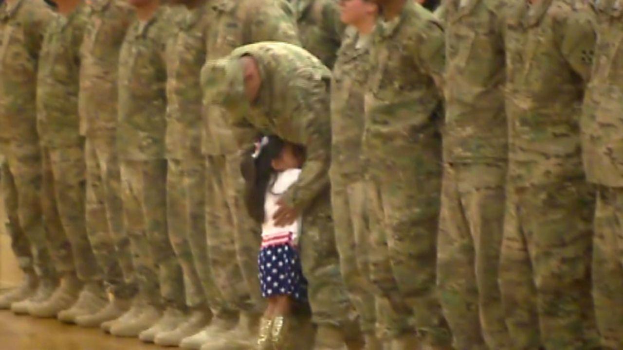 Una niña interrumpe la ceremonia de bienvenida de unos soldados para abrazar a su padre que estaba en formación junto a sus compañeros.
