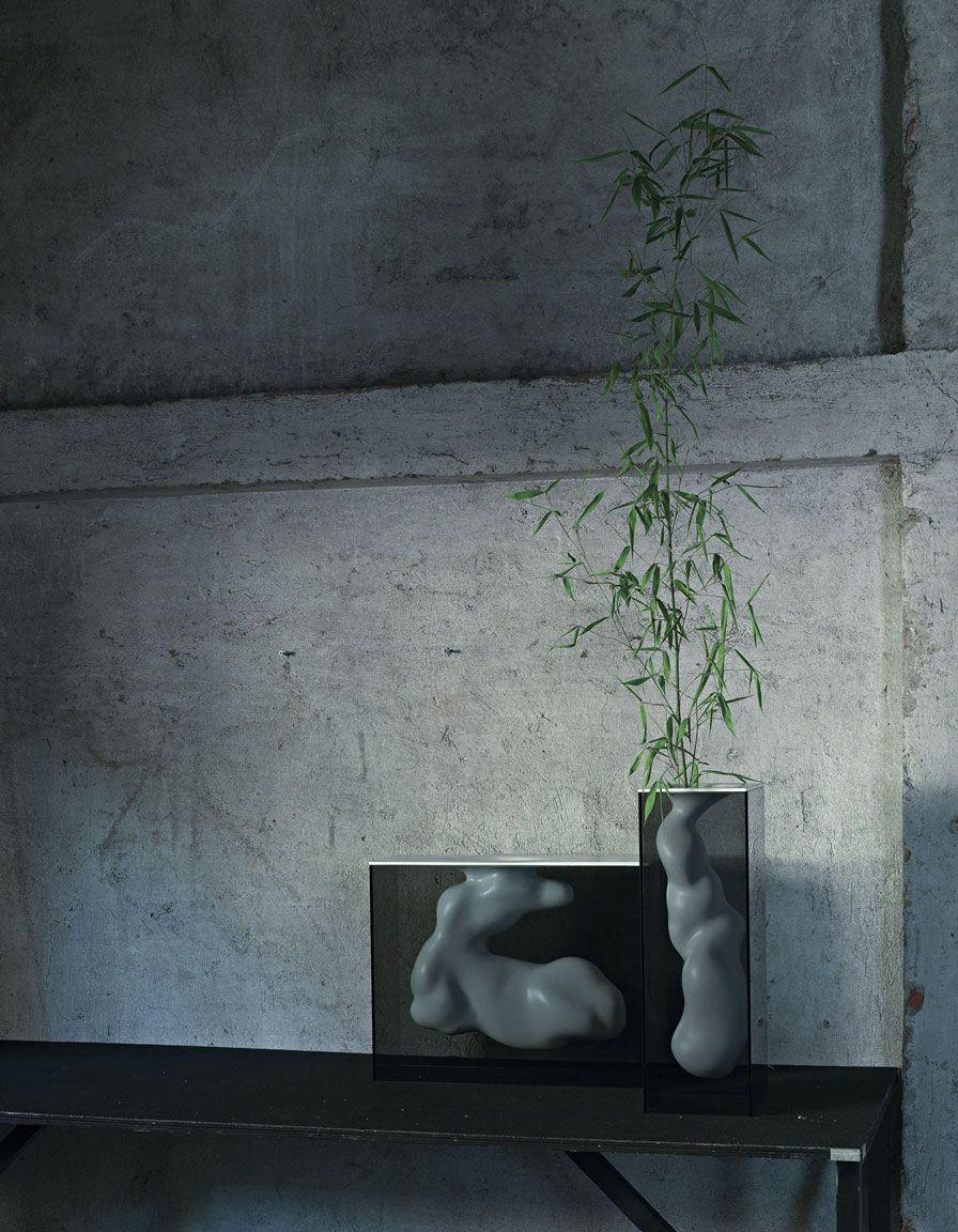 ANGELO E ANGELA Design: Jean-Marie Massaud Vasi composti da un involucro a forma di parallelepipedo, realizzato in cristallo fumè, incollato a 45°, e da una scultura in ceramica di forma organica, sostenuta e contenuta al suo interno. L'elemento in ceramica, disponibile nelle finiture bianco opaco o laccato platino, è cavo e può contenere acqua. Disponibile in due differenti forme e misure