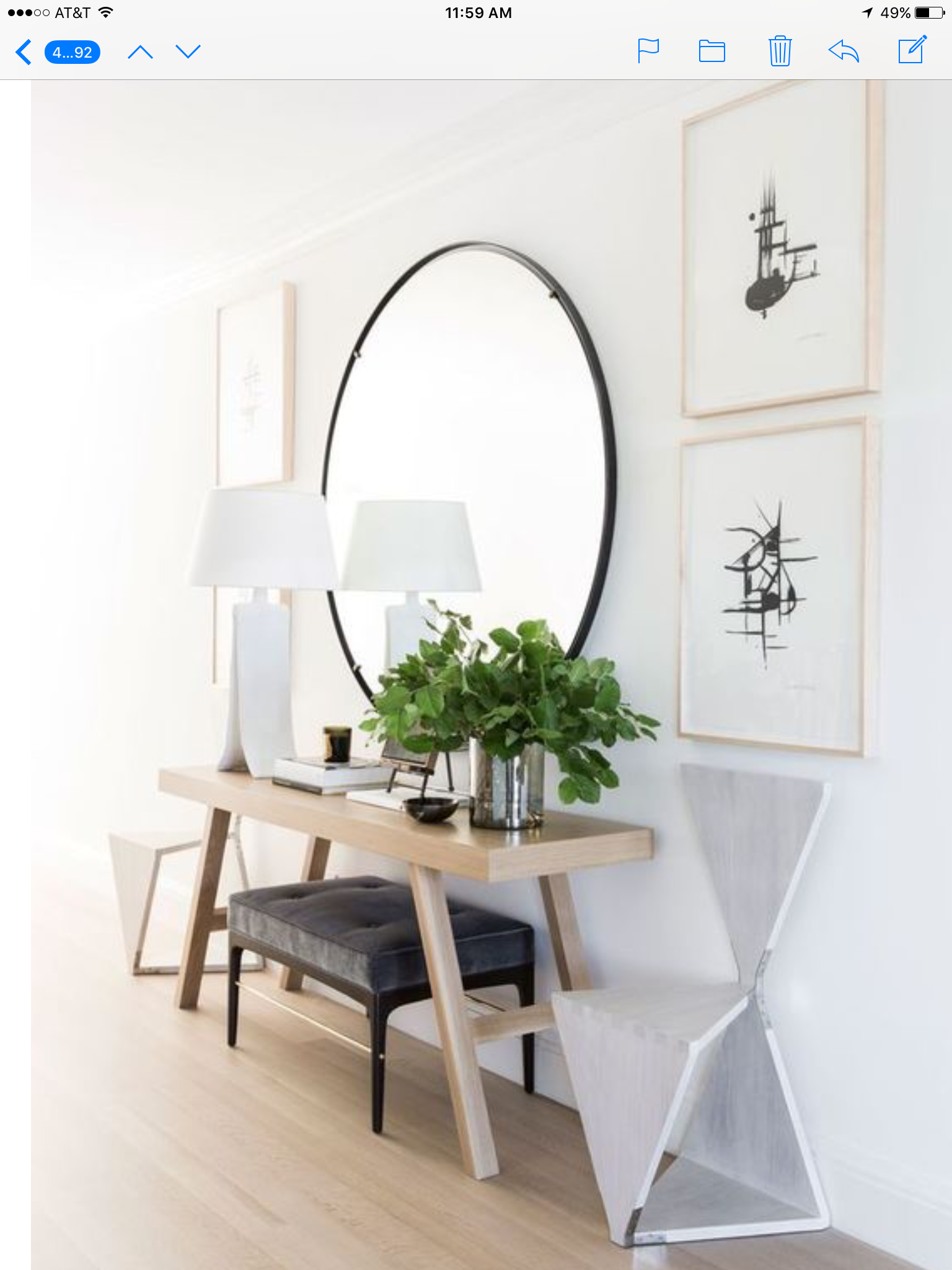 Minimalist Entryway With Oversized Round Mirror Over Light Toned