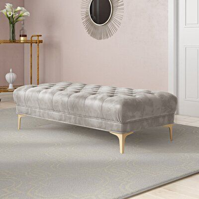 Everly Quinn Create an instant oasis in any living room with this decadent tufted rectangular bench. Extravagant yet versatile, its sumptuous navy velvet upholstery is paired with a classic brass finish on chic modern legs. Use it as a coffee table or extra seating. Upholstery: Gray