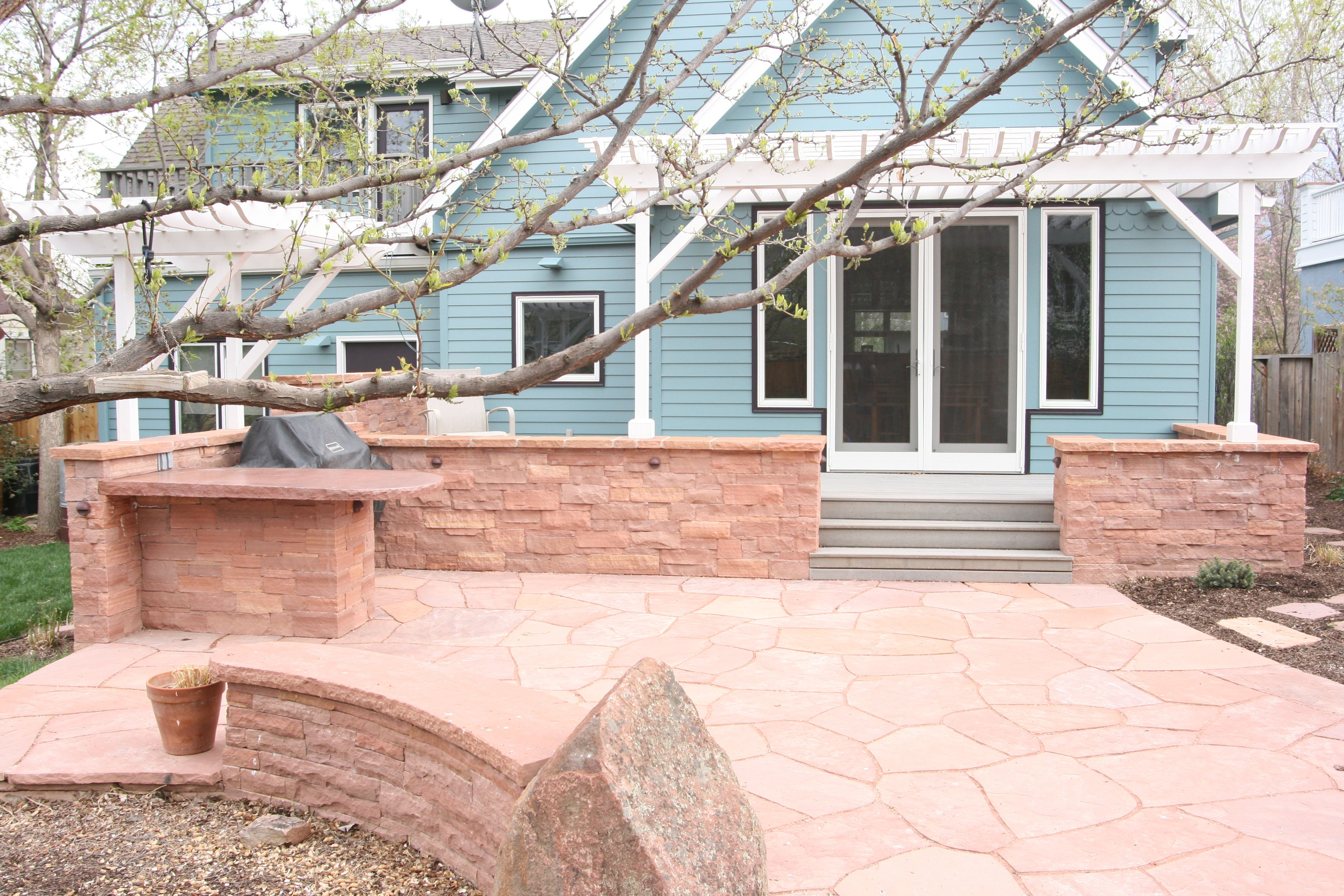 Rose sandstone patio with built-in seat walls and lighting to define the patio area and provide a base for the attached pergola. By Native Edge Landscapes in Boulder, Colorado.