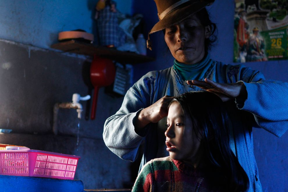"Octavia Ccahuata combs her daughter's hair in the kitchen of their house, which is part of the ""Hot Clean House"" ecology project in the Andean town of Langui in Cuzco, Peru on March 9, 2012. The project uses solar power to warm houses and energy-saving technologies for cooking in the highlands of Cuzco."
