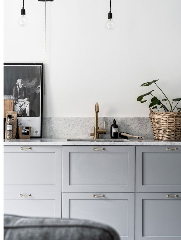 light kitchen with brass tap and marble worktops details. Kitchen styling with green plants and posters.