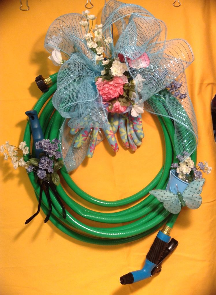 Hose wreath just perfect to hang outside the front door! Blue tones in the accessories. The bow is made of poly deco mesh. Listed on Etsy.