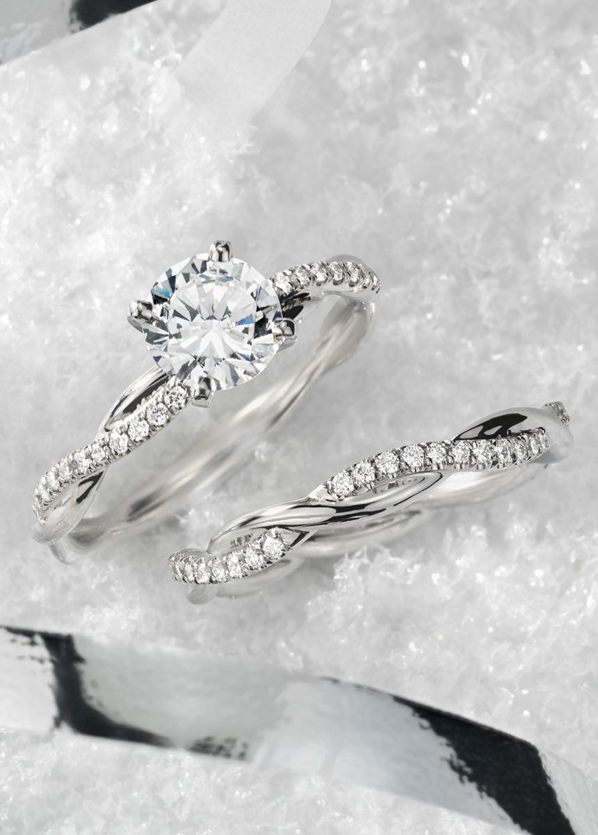 This platinum engagement ring features a delicate twist of pavéset