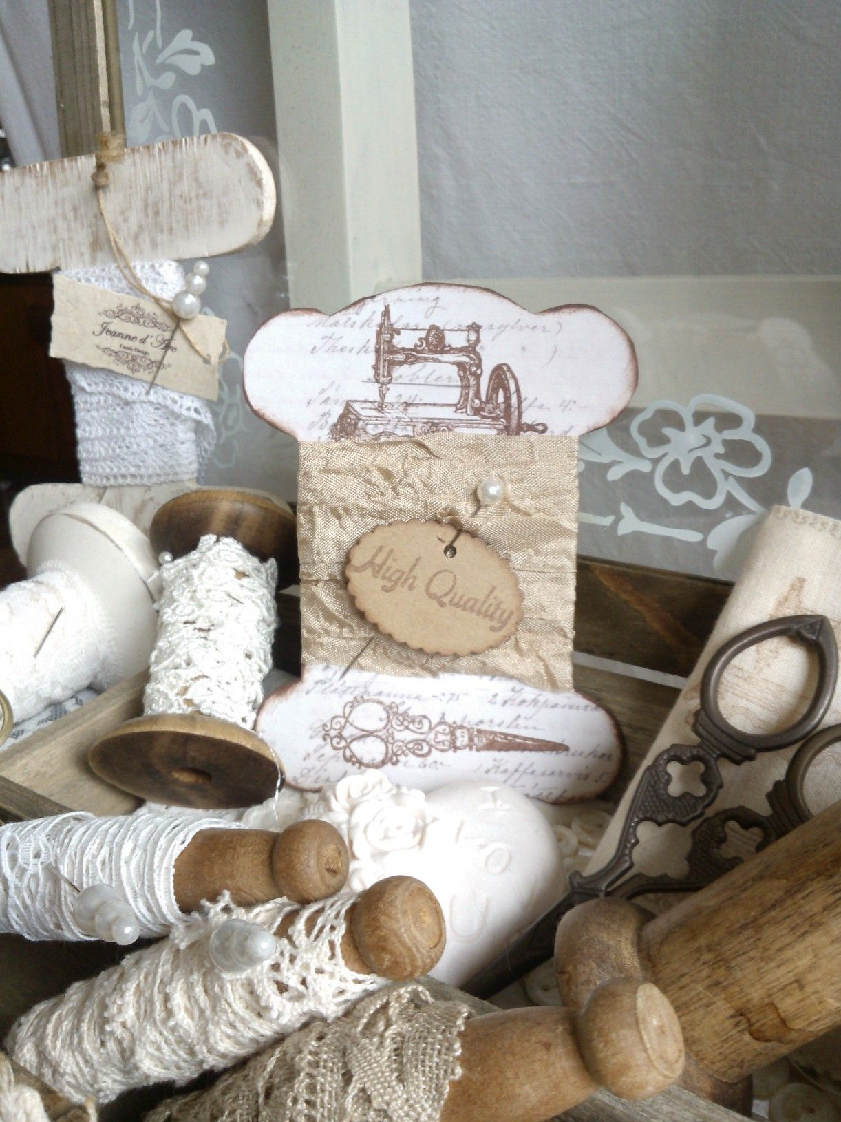 Vintage lace on spools and a thread holder card with sewing drawings.