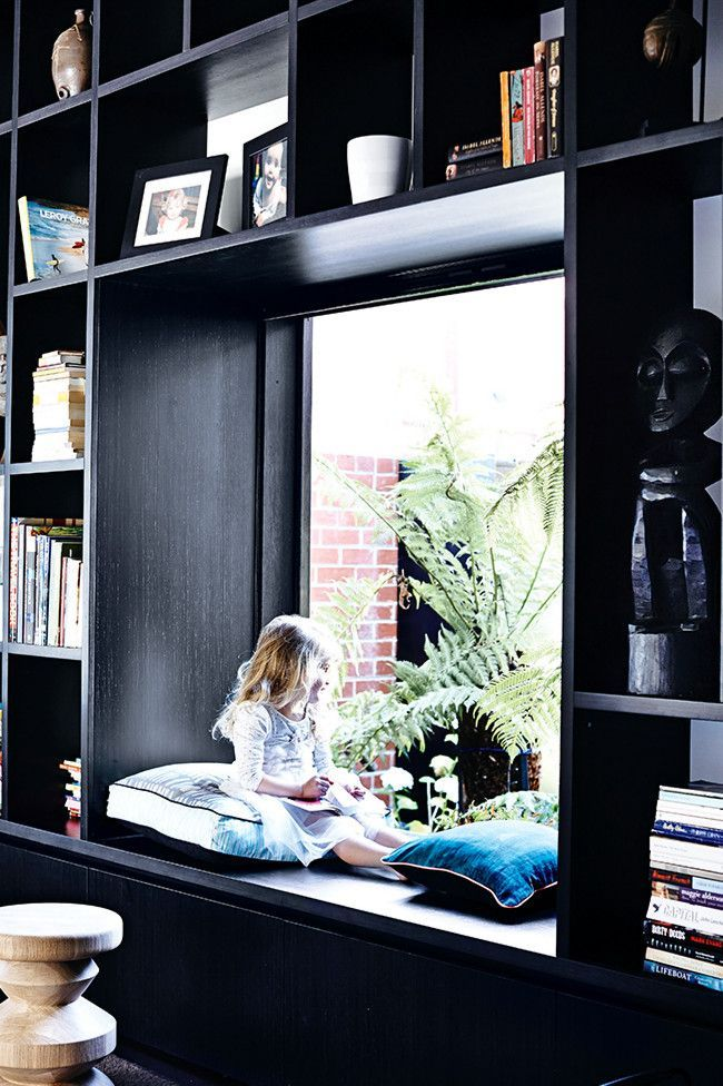 Black wall to wall built in bookcases with the perfect Built in reading nook