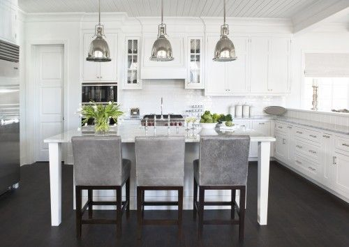 Love the gray leather stools, the crown on the cabinets and their stark whiteness and the light fixtures