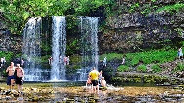 Walkers swimming and walking behind the Sgwd yr Eira waterfall in the Brecon…