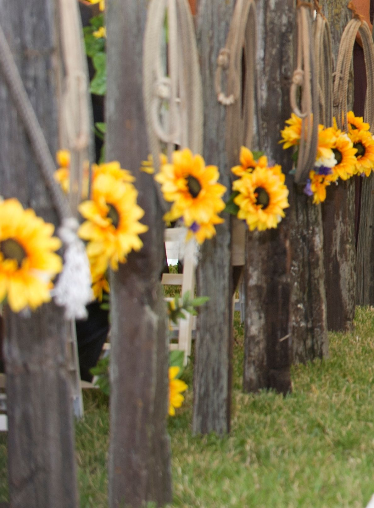 Old Wood Post With Horse Shoe Feet Decorated With Ropes Sunflowers And Ribbon For Aisle At A Pretty Wedding Ceremony Wedding Ceremony Flowers Ceremony Flowers