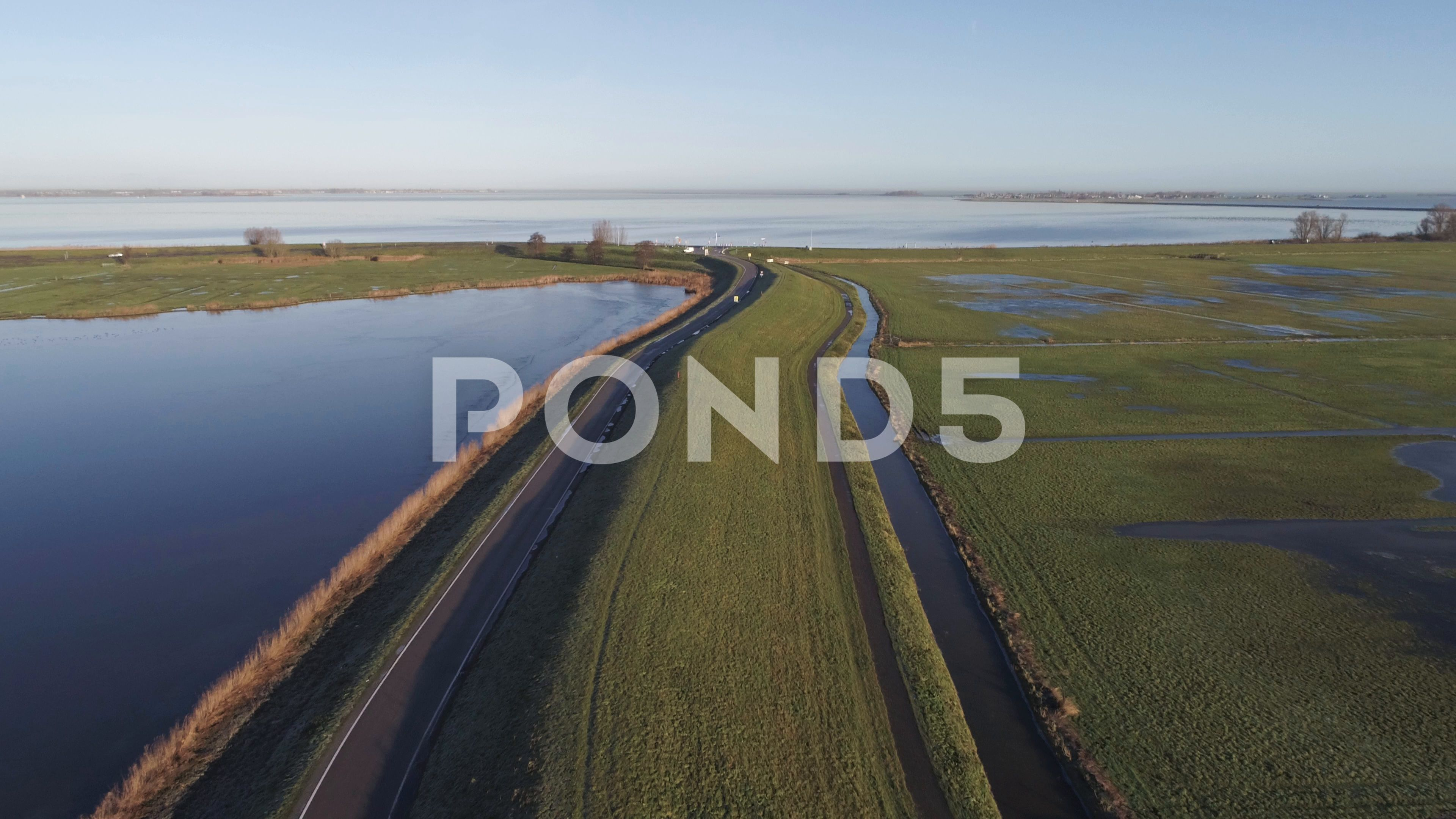 Aerial of an Empty Dutch Countryside Road during Sunset with Ocean in the Stock Footage DutchCountrysideAerialEmpty