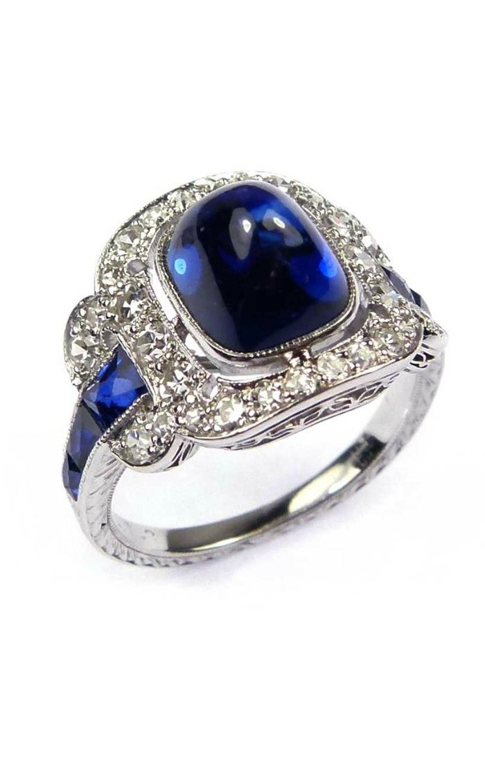 Early 20th century cabochon sapphire & diamond cluster ring, c.1915, the sugarloaf sapphire to a pierced and millegrain set diamond border of cushion outline, graduated French cut sapphire line shoulders with diamond scroll buckle motif, engraved to the shank, traces of a serial number and maker's mark.  At SJ Phillips.