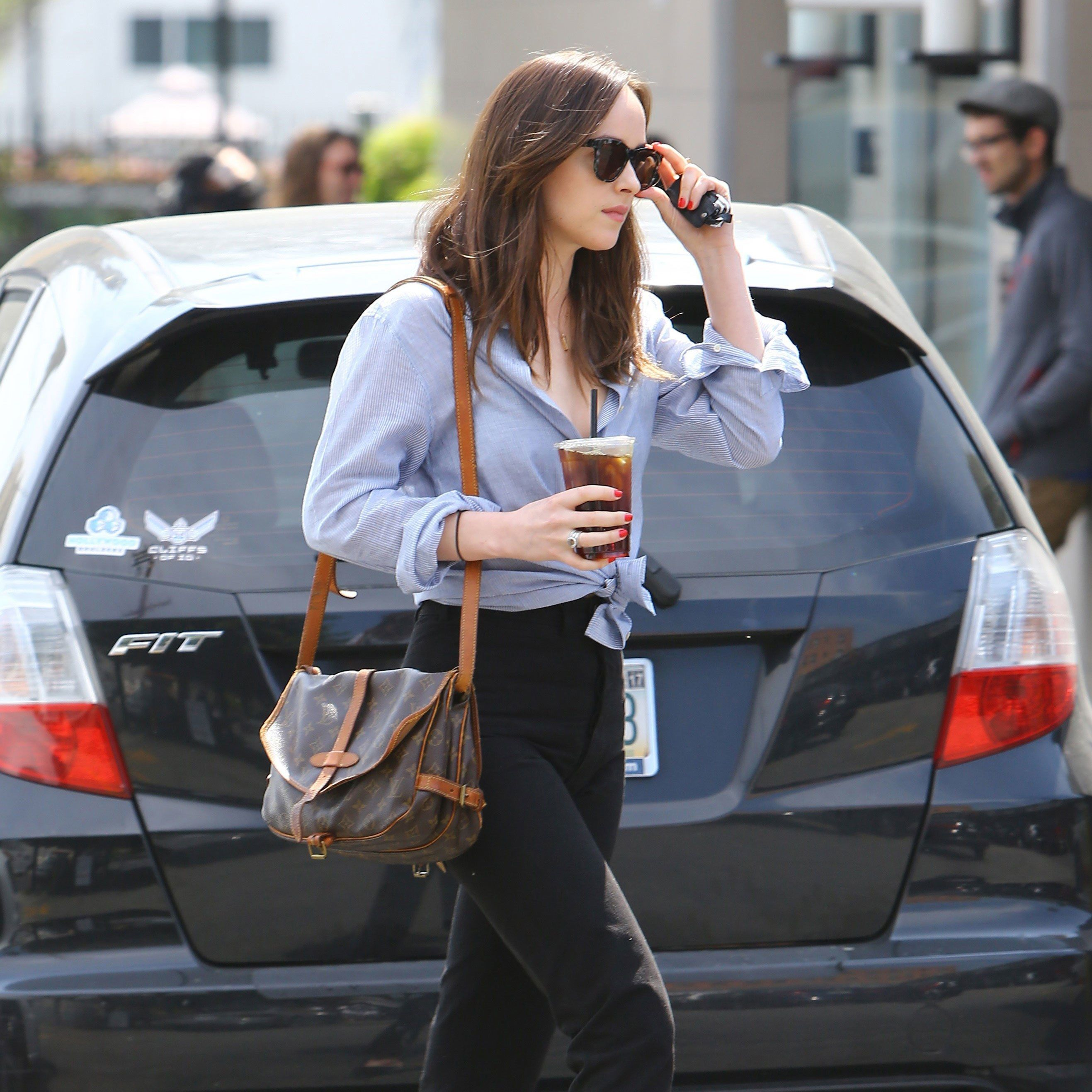 Dakota Johnson in a knotted boyfriend shirt, cigarette trousers, Louis  Vuitton messenger bag and flats.